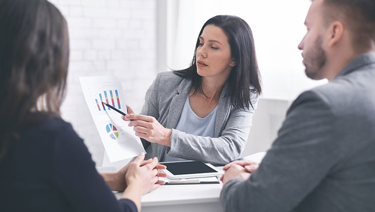 Professional woman giving financial advice to young couple