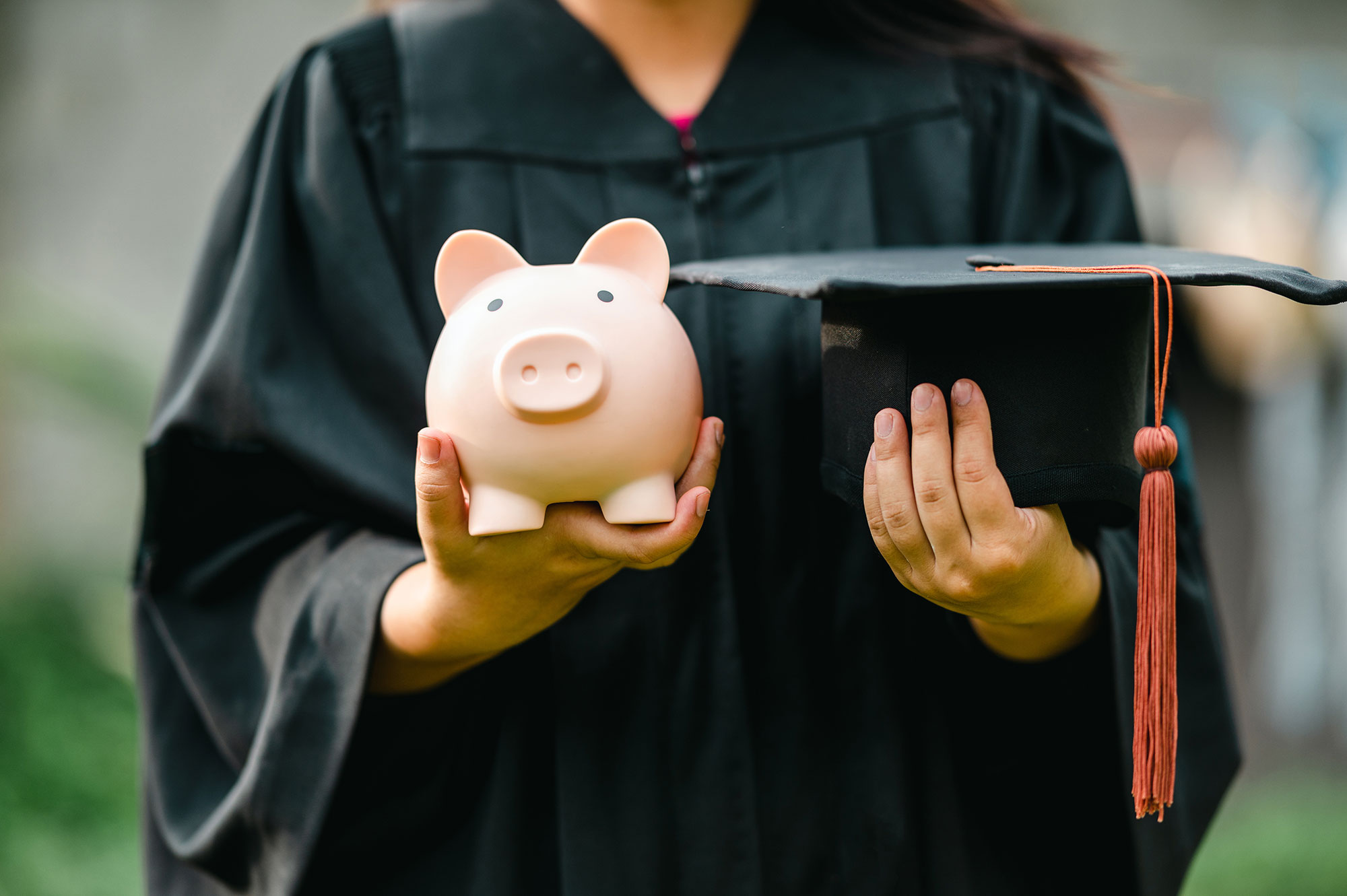 Balancing education and savings. Student a Piggy Bank and a Graduation Cap on each hand.